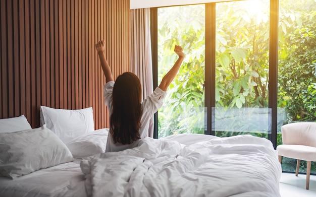 Rückansicht einer frau strecken sich nach dem aufwachen am morgen und betrachten einen schönen naturblick außerhalb des schlafzimmerfensters Premium Fotos