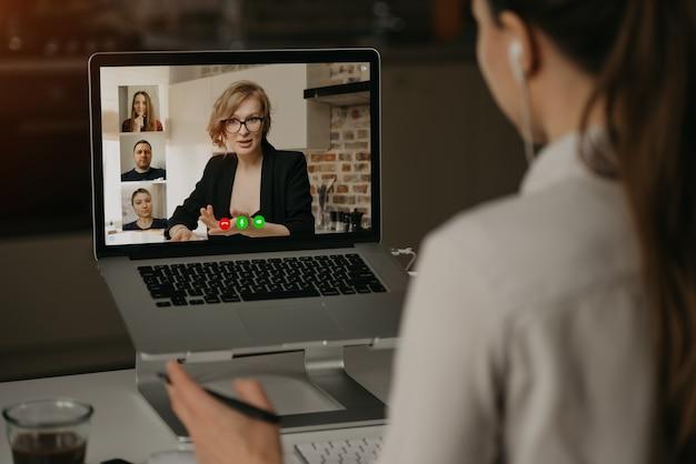 Rückansicht einer frau zu hause, die mit ihrem chef und anderen kollegen in einem videoanruf auf einem laptop spricht. geschäftsfrau spricht mit kollegen auf einer webcam-konferenz. Premium Fotos