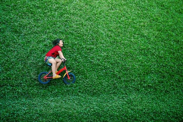 Rückansicht eines glücklichen asiatischen kinder. mädchen auf fahrrad legen am grünen rasen am sommertag nieder Premium Fotos