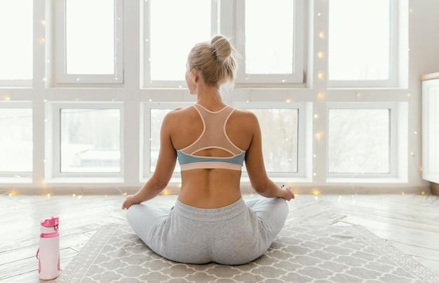 Rückansicht frau auf matte meditieren Kostenlose Fotos