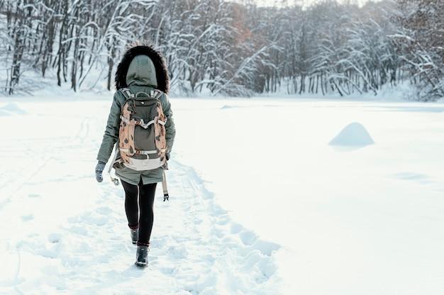 Rückansicht frau mit rucksack am wintertag Kostenlose Fotos