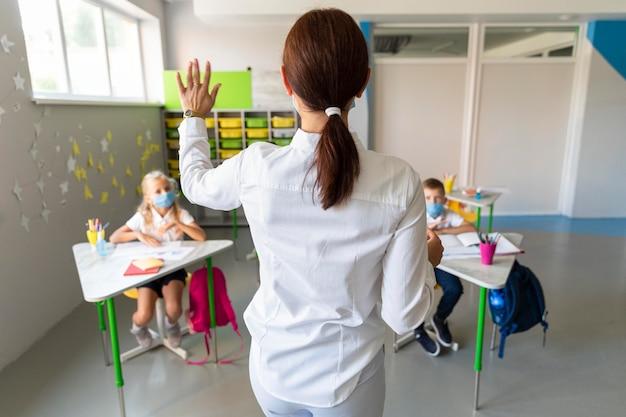 Rückansicht lehrer warten auf eine antwort in der klasse Kostenlose Fotos