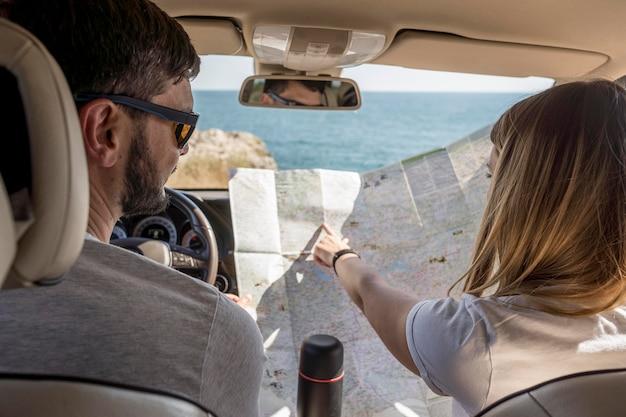 Rückansicht personen, die auf einer karte suchen, um ein neues ziel zu finden Kostenlose Fotos