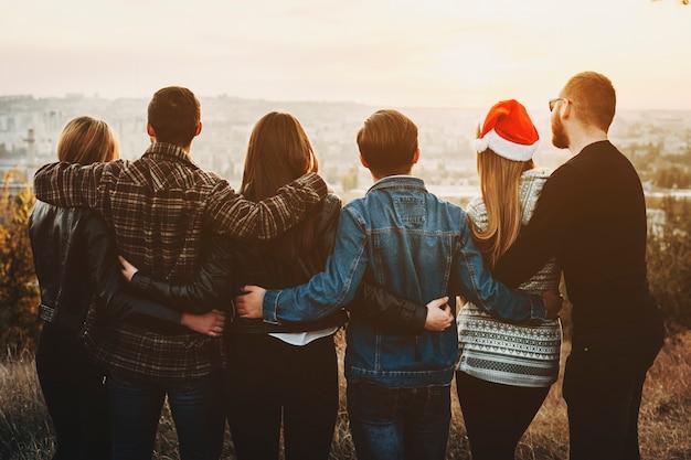 Rückansicht von jungen männern und frauen, die einander umarmen und die moderne stadt betrachten, während weihnachten zusammen feiern Premium Fotos