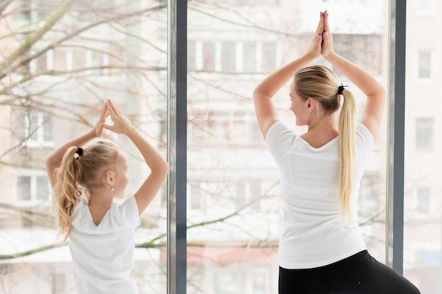 Rückansicht von mutter und tochter in yoga-pose Kostenlose Fotos