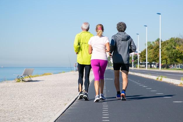 Rückansicht von reifen joggern in sportkleidung, die auf spur entlang flussufer laufen. kopierraum in voller länge. aktivitäts- oder lebensstilkonzept Kostenlose Fotos