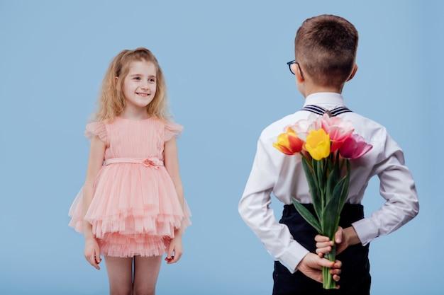 Rückansicht, zwei kleine kinderjunge mit blumen und mädchen im rosa kleid, lokalisiert auf blauer wand Premium Fotos