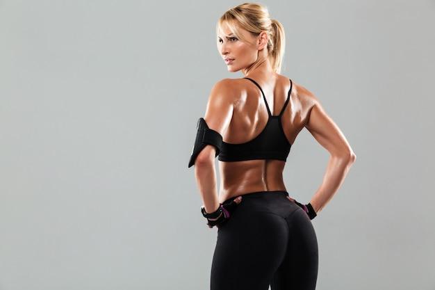 Rückansichtporträt einer gesunden muskelsportlerin stehend Kostenlose Fotos