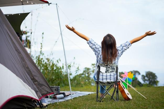Rückseite der asiatischen frau, die auf picknickstuhl sitzt und mit schöner natur beim camping mit der familie auf dem campingplatz genießt. Premium Fotos