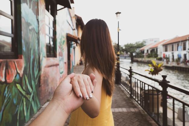 Rückseite der frau die mannhand halten, die für reise in malakka, malaysia führt Premium Fotos