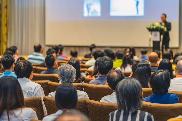 Rückseite des publikums hört der sprecher auf der bühne Premium Fotos