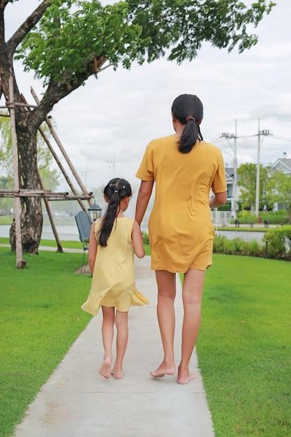 Rückseite von mutter und tochter hand in hand entspannen im garten im freien spazieren gehen. mutter und kind verbringen zeit zusammen im sommerpark Premium Fotos
