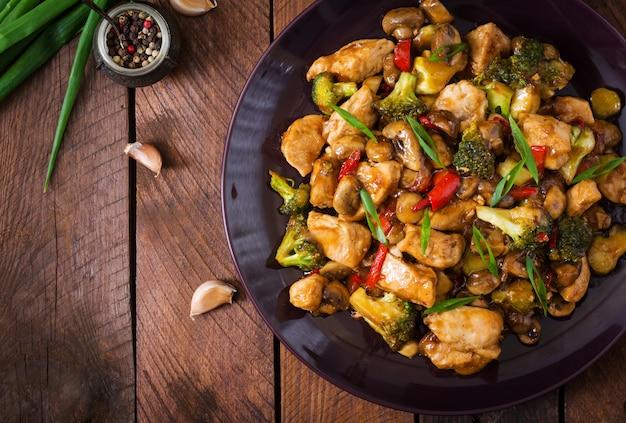 Rühren sie braten mit huhn, pilzen, brokkoli und pfeffern - chinesisches lebensmittel. ansicht von oben Premium Fotos