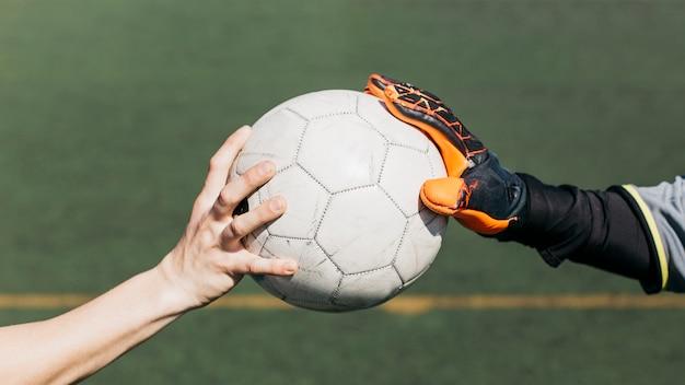 Rührender ball des fußballspielers und des torhüters Kostenlose Fotos