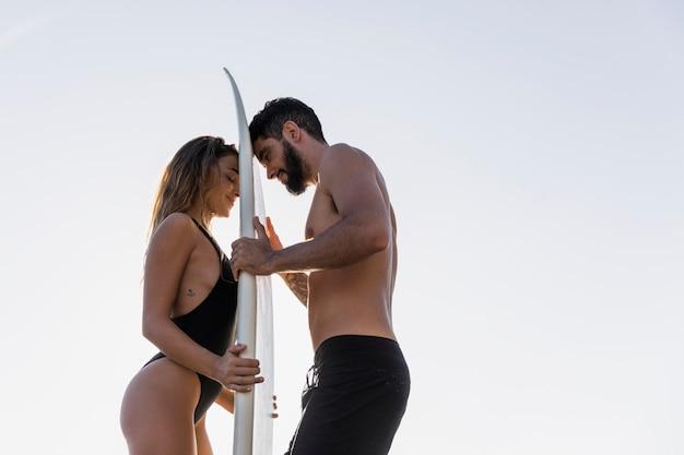 Rührendes surfbrett der jungen paare mit stirnen Kostenlose Fotos