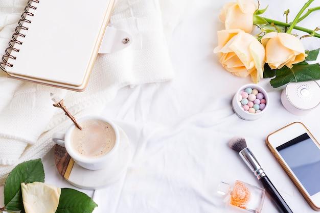 Rufen sie, weißer tasse kaffee und rosen mit notizbuch auf weißem bett und plaid, gemütliches morgenlicht an. Premium Fotos