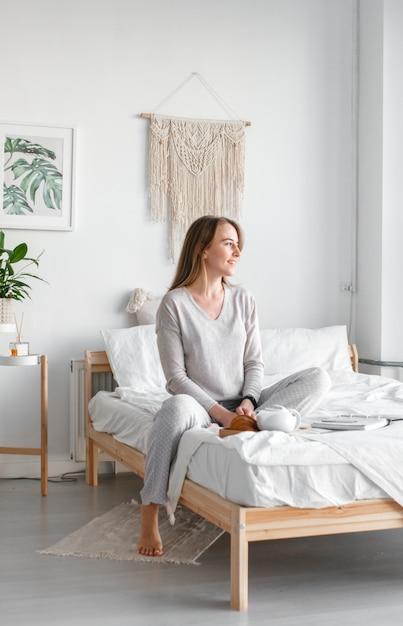Ruhe dich nach einem anstrengenden arbeitstag aus. schöne junge lächelnde geschäftsfrau im pyjama, die kaffee trinkt und wegschaut, während sie auf einem bett in einem weißen raum sitzt. Premium Fotos