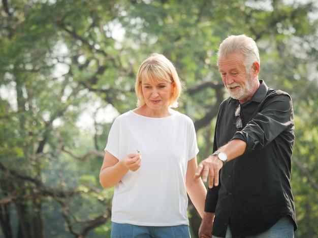 Ruhestand mit zwei glücklicher senioren mann und frau gehen und sprechen im park Premium Fotos