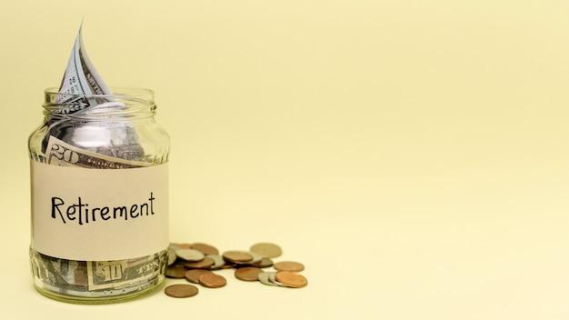 Ruhestandsaufkleber auf einem glas füllte mit vorderansicht des geldes und kopienraum Kostenlose Fotos