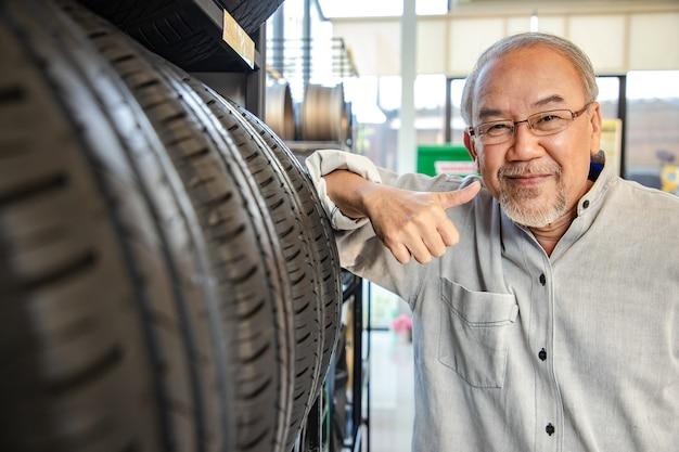 Ruhestandsmann, der berührt und für den kauf eines reifens in einem supermarkt-einkaufszentrum wählt. gummi-autorad messen. Premium Fotos