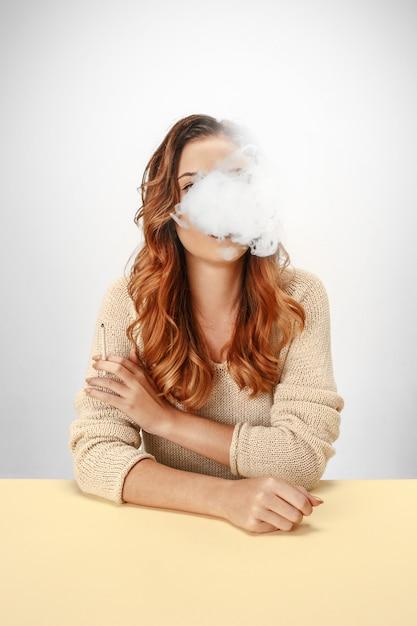 Ruhige frau, die am tisch sitzt und raucht. Kostenlose Fotos