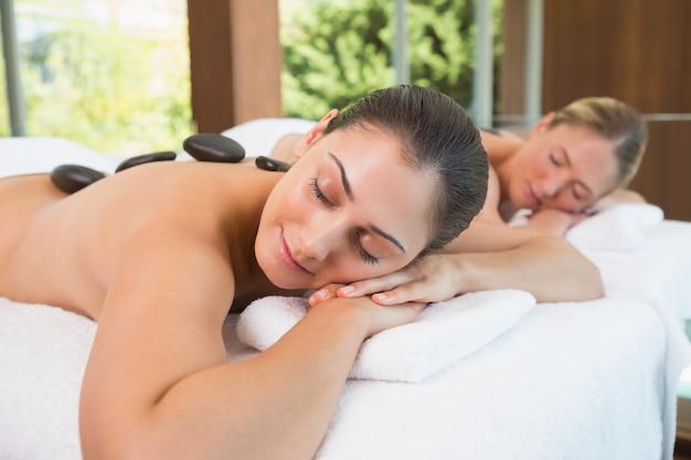 Ruhige freunde liegen auf massagetischen mit heißen steinen auf dem rücken Premium Fotos
