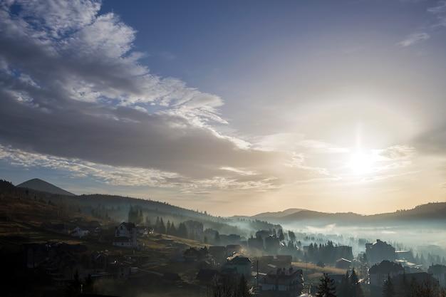 Ruhige nebelhafte landschaft, ländliches herbstpanorama unter hellem blauem himmel an der dämmerung oder an der dämmerung. schöne, im bau befindliche ferienhäuser in einem nebligen tal mit bewaldeten hügeln und bergen am horizont. Premium Fotos