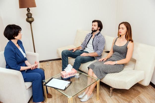 Ruhige und friedliche menschen sitzen mit geschlossenen augen zusammen. sie arbeiten mit einem psychologen zusammen. doktor schaut zu den jungen paaren und spricht mit ihnen. Premium Fotos