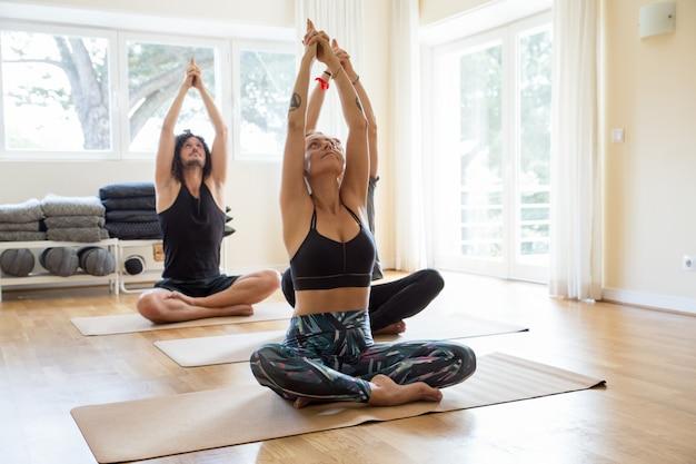 Ruhige yogaliebhaber, die in der turnhalle ausbilden Kostenlose Fotos