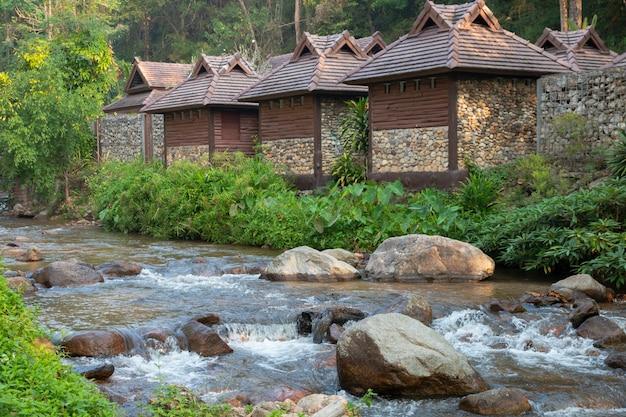Ruhiger bergwasserstrom, der mit holzhaus fließt. Premium Fotos