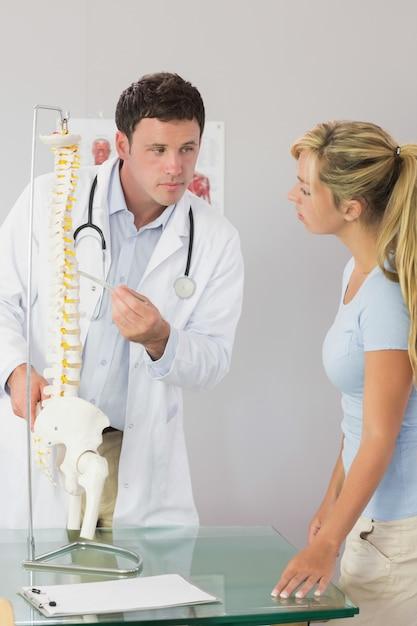 Ruhiger doktor, der einem patienten etwas auf skeleton modell zeigt Premium Fotos