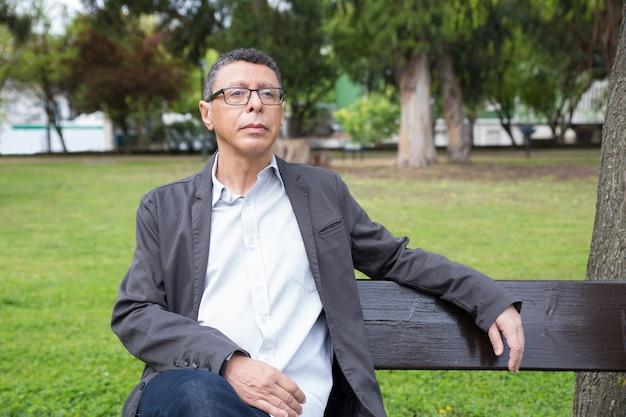Ruhiger mann von mittlerem alter, der auf bank im park sitzt und sich entspannt Kostenlose Fotos