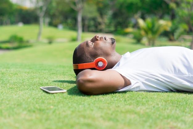 Ruhiger schwarzer mann, der im park stillsteht und musik hört. Kostenlose Fotos