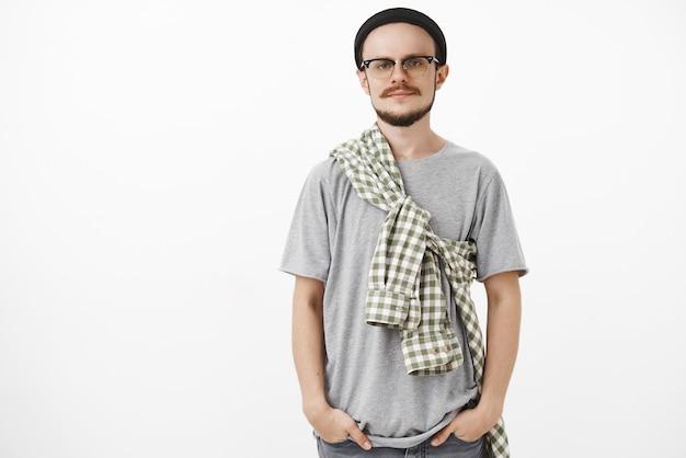 Ruhiger und kühler kreativer europäischer mann mit bart in gläsern und schwarzer mütze, die hände in den taschen hält, die vor gleichgültigkeit grinsen und vor gleichgültigkeit herumblicken Kostenlose Fotos