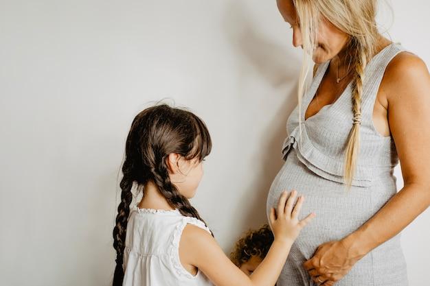 Rührender Bauch des Mädchens der schwangeren Mutter Kostenlose Fotos