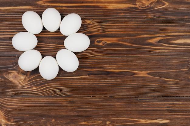 Rund gemacht von den weißen eiern auf holztisch Kostenlose Fotos