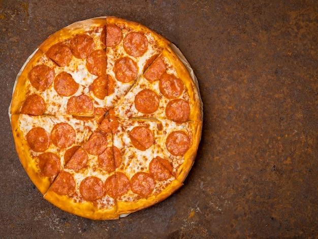 Runde italienische pizza pepperoni auf einer rostigen metalltischplattenansicht, leerer raum für text. Premium Fotos