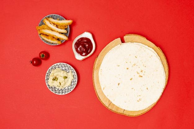 Runde tortilla mit dips neben brathähnchen Kostenlose Fotos