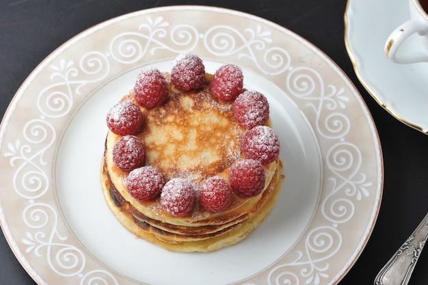Runder kuchen mit himbeeren und tasse tee Premium Fotos