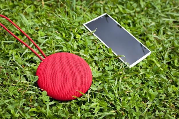 Runder musik bluetooth sprecher mit dem smartphone, der auf dem gras liegt. Premium Fotos