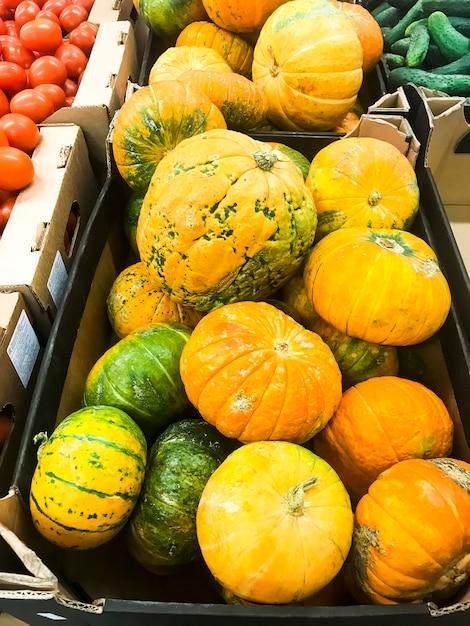 Runder orange kürbis auf supermarktregalen, verkauf. Premium Fotos