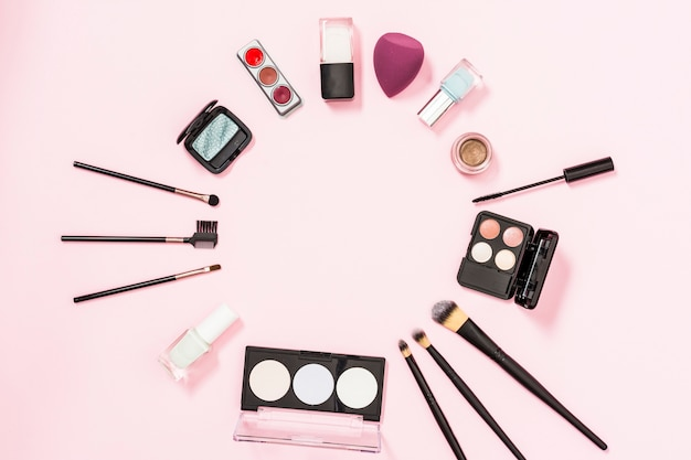 Runder rahmen mit make-up-pinseln; nagellackflasche; lidschatten; mixer auf rosa hintergrund Kostenlose Fotos