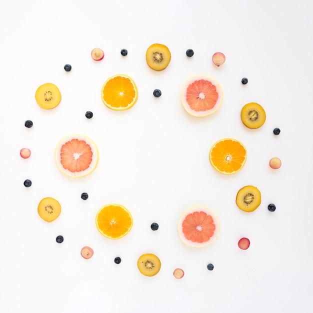 Runder rahmen mit orange gemacht; trauben; kiwi; grapefruit und blaubeeren auf weißem hintergrund Kostenlose Fotos