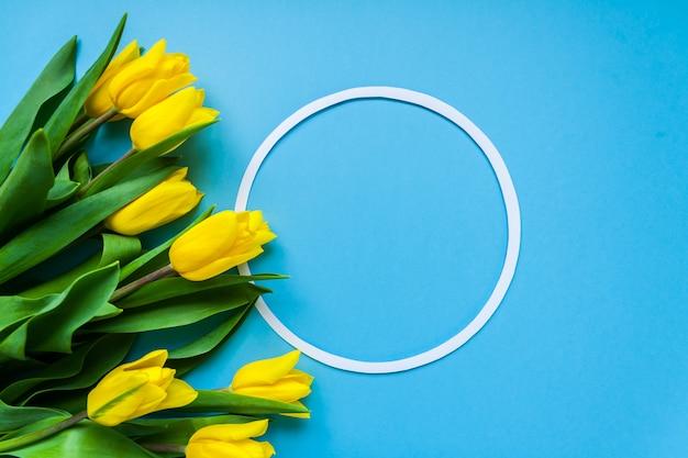 Runder rahmen und gelbe tulpen auf blauem copyspace hintergrund Premium Fotos