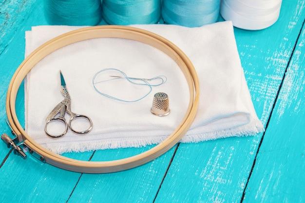 Runder stickrahmen aus holz und weißer stoff zum kreuzsticken Premium Fotos
