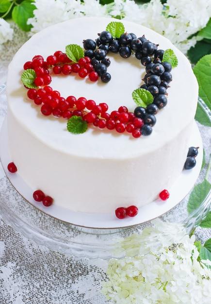 Runder weißer kuchen mit beeren in form von herzen, valentinstag, auf weißer oberfläche. bild für ein menü oder einen süßwarenkatalog. ansicht von oben Premium Fotos