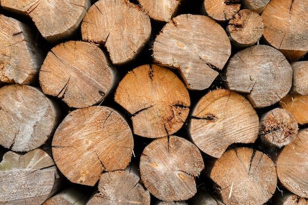 Rundes brennholz auf holzstapel gestapelt. holzstruktur und hintergrund. Premium Fotos