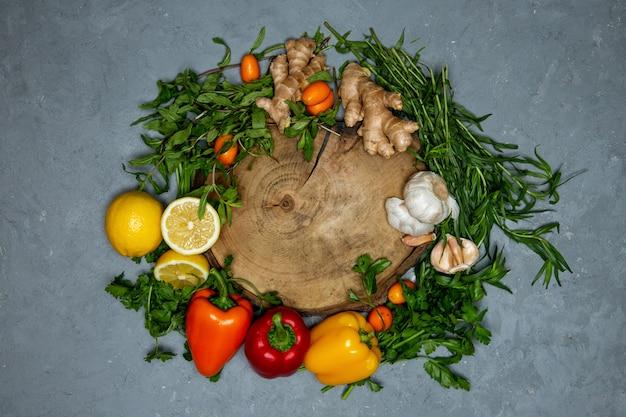 Rundes holzbrettset mit frischem gemüse, zitrusfrüchten und ingwer auf grauer draufsicht Kostenlose Fotos