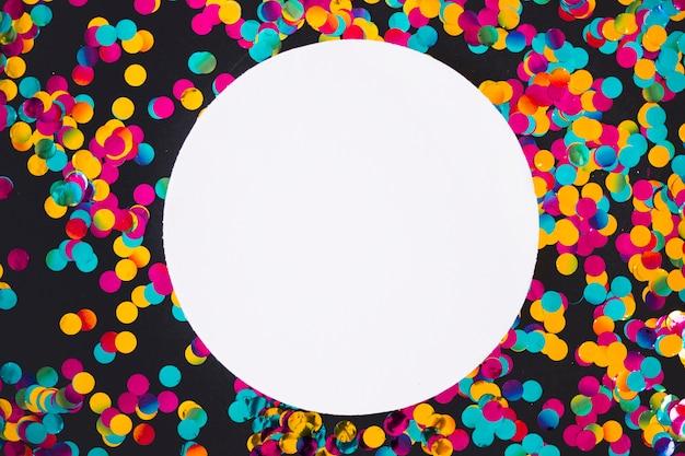 Rundes papier mit verstreuten hellen pailletten Kostenlose Fotos