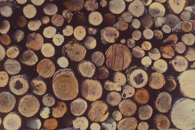 Rundes ungebrochenes brennholz gestapelt in einem holzstapel Premium Fotos